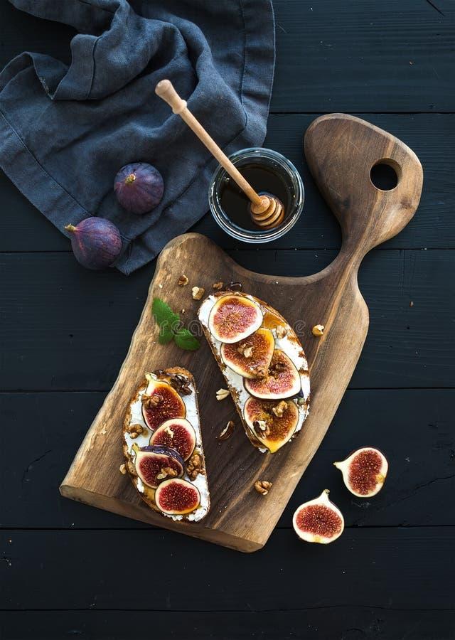 Smörgåsar med ricotta, nya fikonträd, valnötter och royaltyfri bild