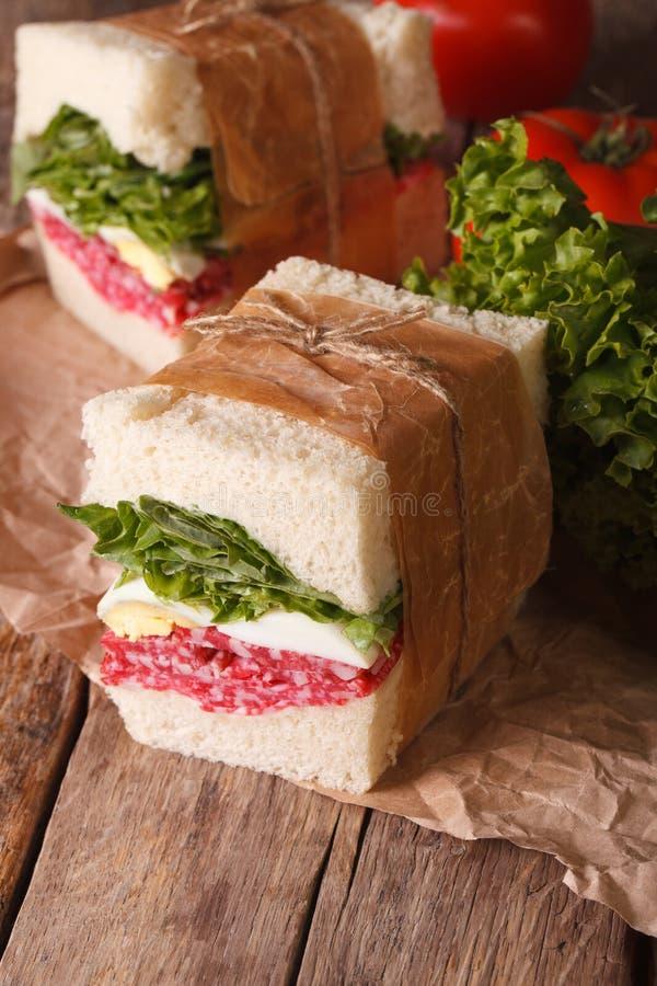 Smörgåsar med salami, grönsallat och ägget som slås in i papper arkivbild