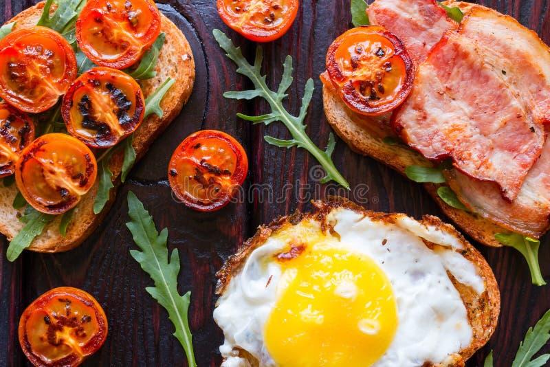 Smörgåsar på en svart bakgrund dekorerade med grillad tomater och arugula arkivbilder
