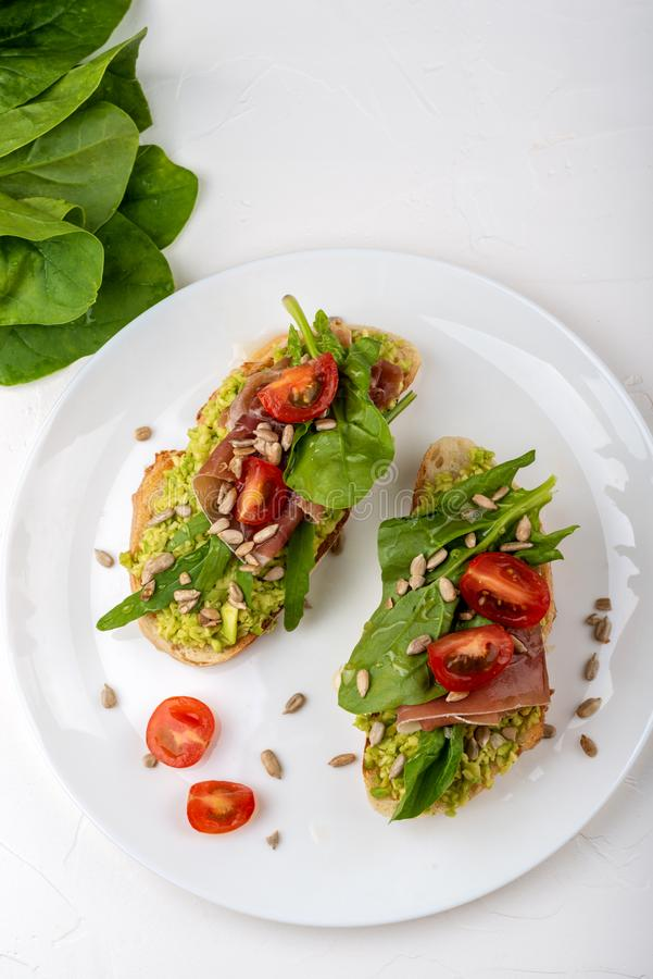 Smörgåsen med ibericaen för paletaen för jamonskinkaserranoen, arugula, rosmarin på stenen kritiserar svart bakgrund Top besk?dar arkivfoton