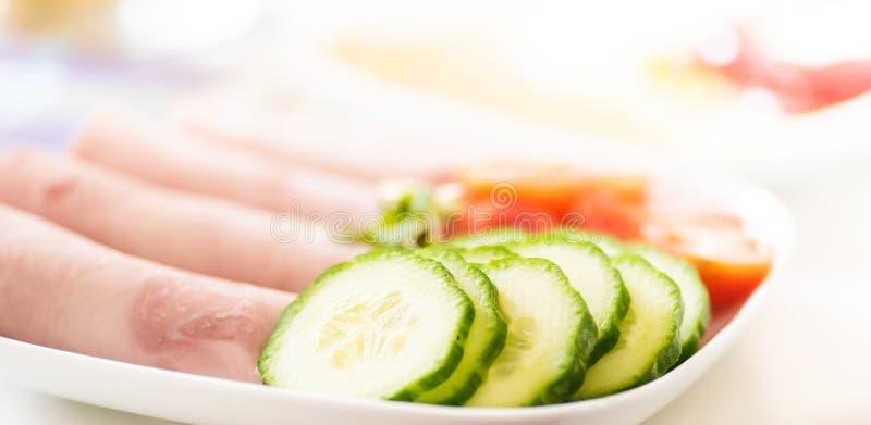 Smörgåsfyllningar för lunch - skivad gurka, tomatoe och skinka på den vita plattan royaltyfria bilder