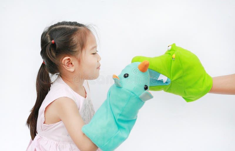 Sm? asiatiska barnflickah?nder som spelar djura dockor med handen av hennes moder p? vit bakgrund Utbildningsbegrepp royaltyfri foto