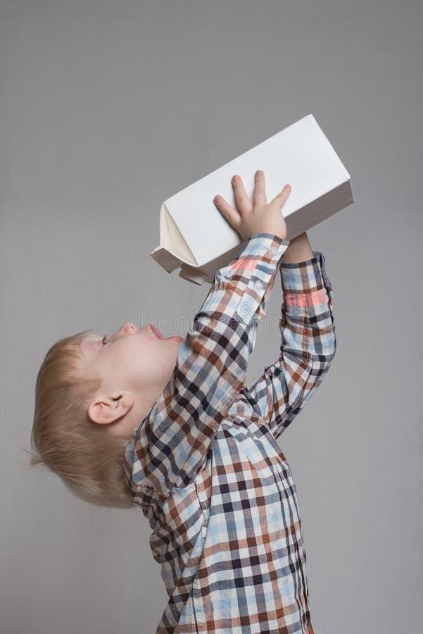 Sm? blonda pojkedrinkar fr?n en stor vit packe Ljus bakgrund arkivfoto