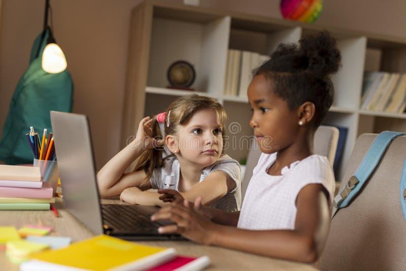 Sm? flickor som g?r l?xa p? en b?rbar datordator fotografering för bildbyråer