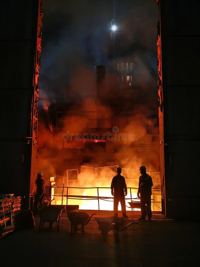 Sm?ltning av metall i stor gjuteri J?rn- och st?lproduktion p? en metallurgical v?xt St?larbetare Metallurgiprocess arkivfoton