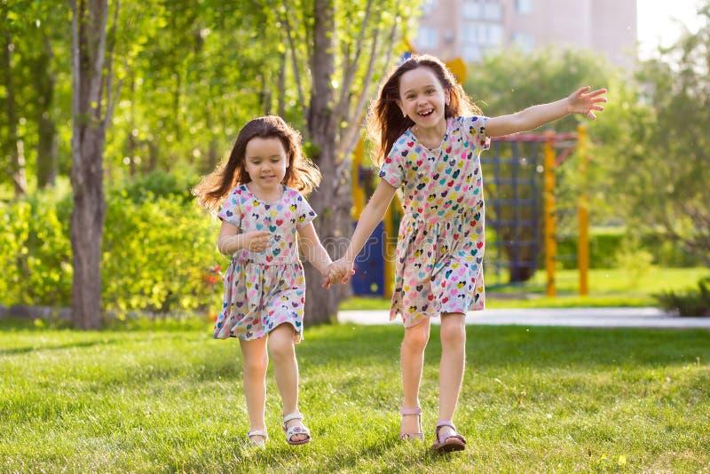 Sm? lyckliga flickor p? g?r p? en sommarafton p? solnedg?ngen i parkerar systrar arkivbild