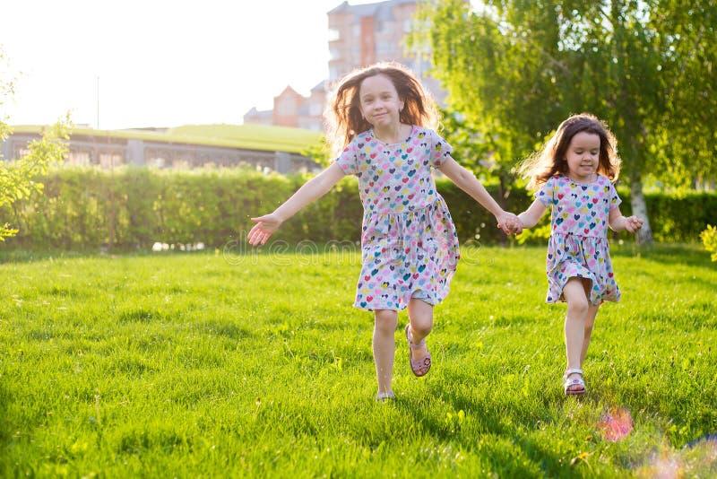Sm? lyckliga flickor p? g?r p? en sommarafton p? solnedg?ngen i parkerar systrar royaltyfri fotografi