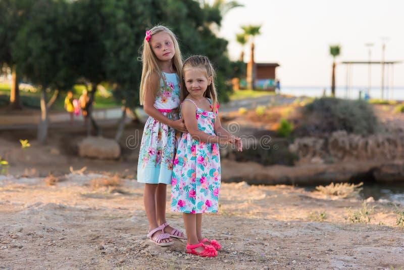 Sm? lyckliga flickor p? g?r p? en sommarafton p? solnedg?ngen i parkerar systrar unga vuxen m?nniska ferier royaltyfria bilder