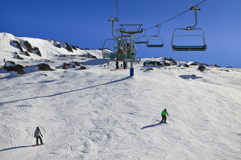 SM Top Chair Lift Skiers. Snowy mountains chair lift up to the top of mountain at winter with white show and skiyng ski resort snowboarders stock photography