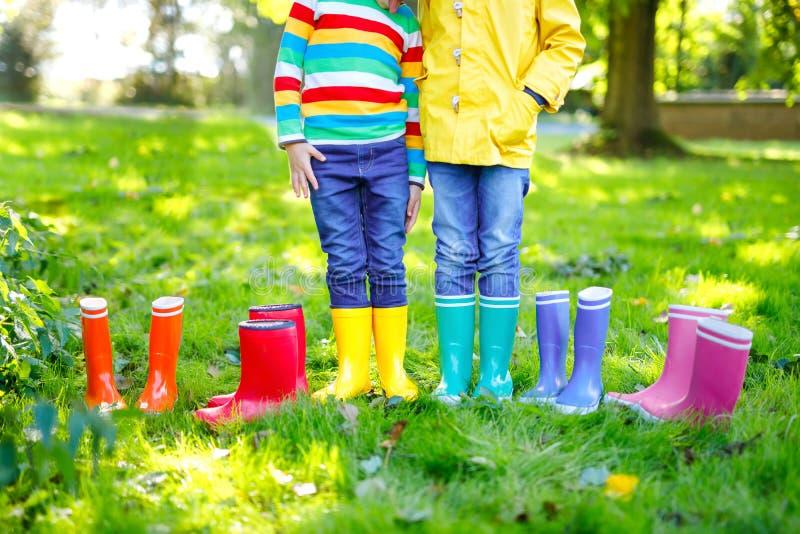 Sm? ungar, pojkar och flickor i f?rgrika regnk?ngor N?rbild av barn i olika gummist?veler, jeans och omslag royaltyfri fotografi