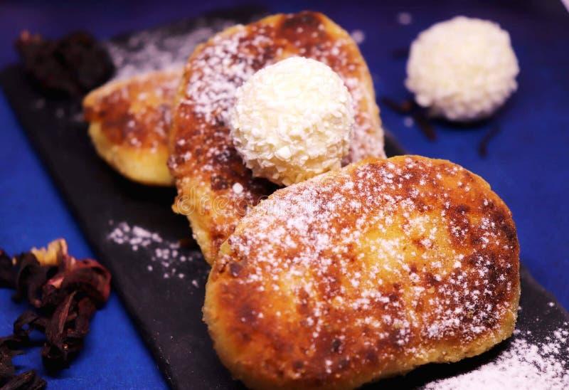 Smażący cheesecakes pudrujący z sproszkowanym cukierem z dodatkiem wyśmienicie raffaello w górę błękitnego tła, dalej zdjęcie stock