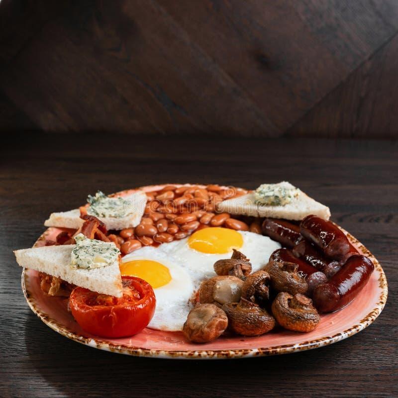 Smażący szampiniony, smażący jajka, soczyste kiełbasy, smażący bekon, grzanka z masłem i bejcować fasole w pomidorowym kumberland zdjęcia stock
