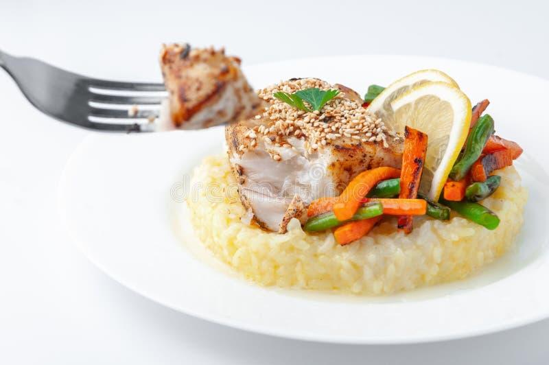 Smażąca żerdź polędwicowa z ryż i warzywami Na rozwidleniu kawałek polędwicowy jest z ostrości Na białym talerzu Biały tło zdjęcie stock