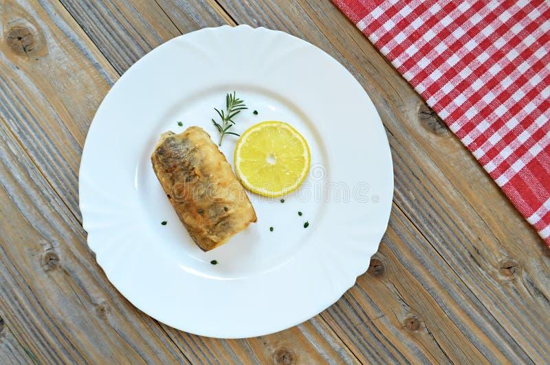 Smażąca morszczuk ryba, plasterek cytryna i rozmaryny na talerzu, obraz royalty free