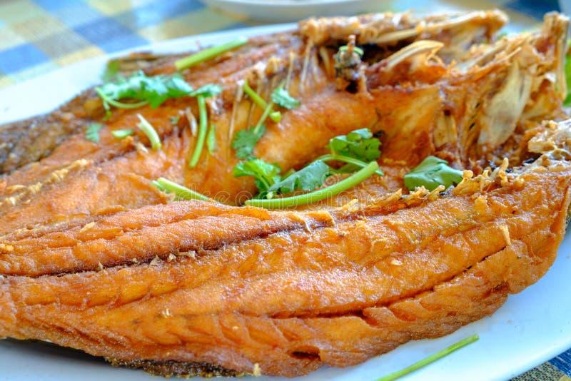 Smażąca ryba słuzyć w talerzu umieszczającym na stole fotografia royalty free
