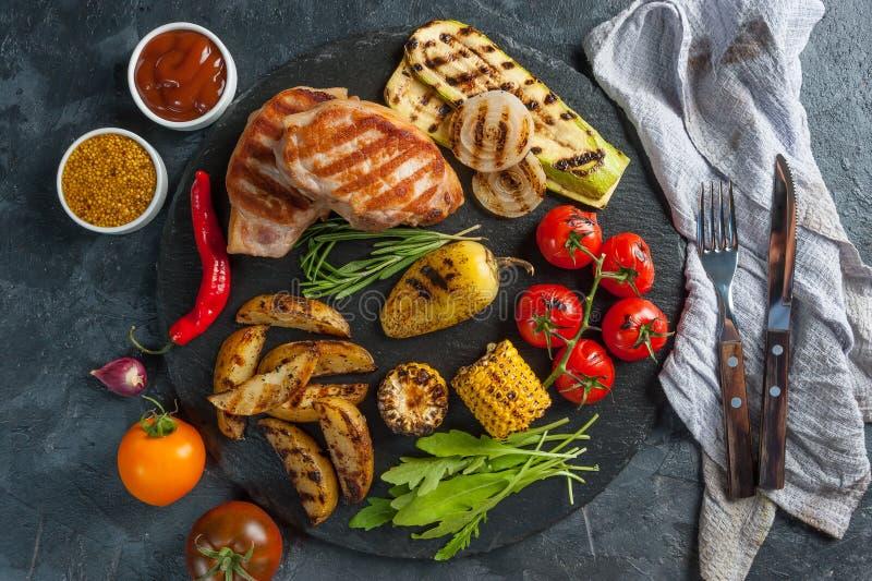 Smażącej wieprzowiny polędwicowi i piec na grillu warzywa zdjęcie stock