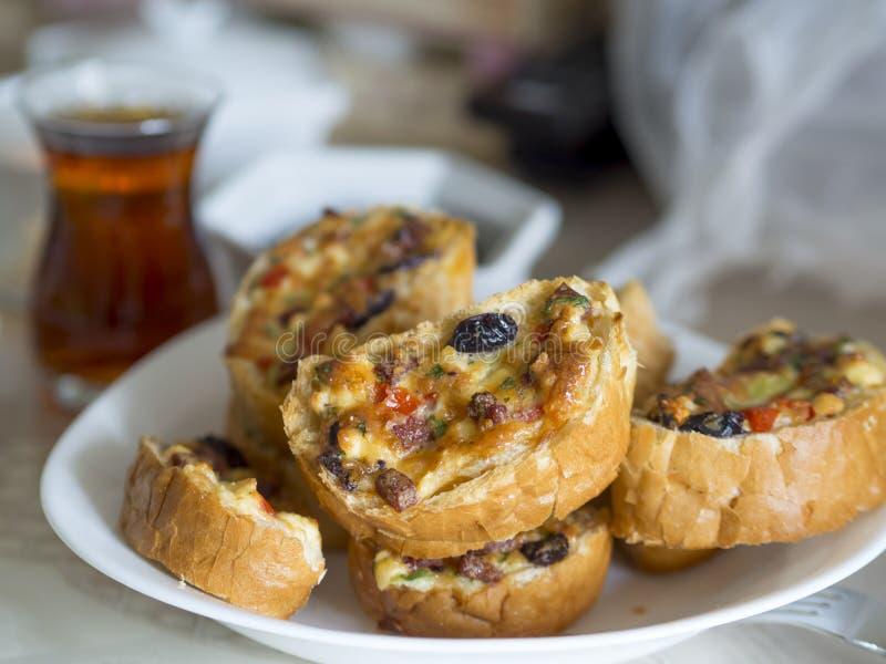 Smażący śniadaniowi chlebów plasterki w piekarnika, jajka, sera, oliwek, pomidoru i kiełbasy kawałkach, obrazy stock