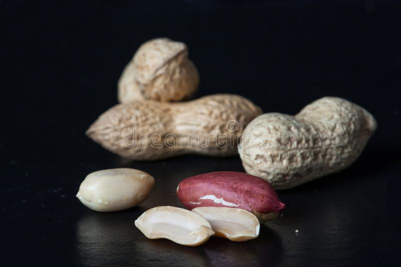 Smażący arachidy w czarnym tle Organicznie Zdrowe fasole fotografia stock