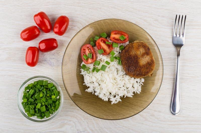 Smażący cutlets z ryż, pomidory, puchar z zieloną cebulą, rozwidlenie zdjęcie royalty free