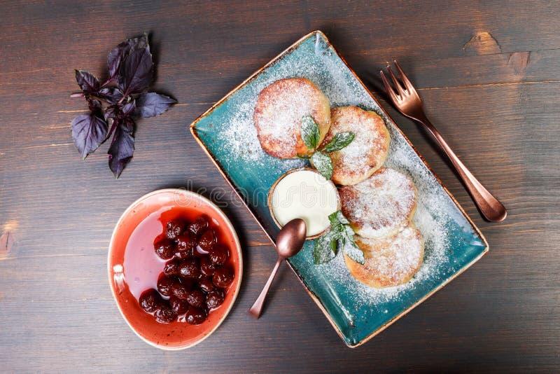 Smażący domowej roboty chałupa sera blinów syrniki z sproszkowanym cukierem, kwaśna śmietanka, jagody przyskrzynia na talerza zak zdjęcie royalty free