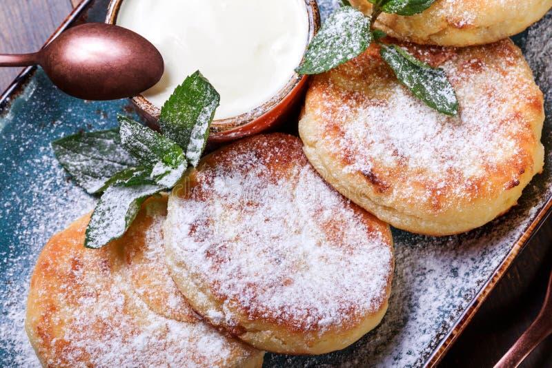 Smażący domowej roboty chałupa sera blinów syrniki z sproszkowanym cukierem, kwaśna śmietanka, jagody przyskrzynia na talerza zak zdjęcia stock