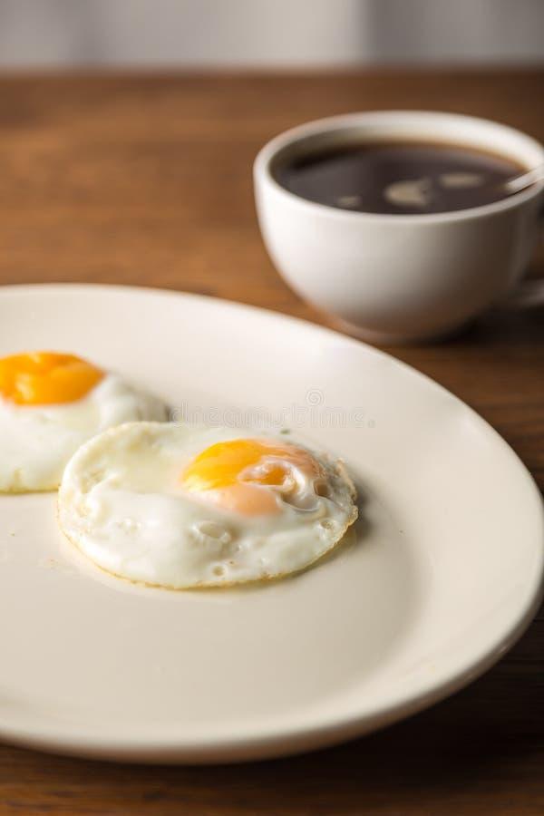 Smażący jajka na bielu talerzu i filiżance czarna kawa dla śniadania na drewnianym tle obrazy royalty free