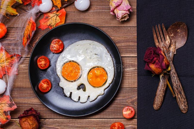 Smażący jajka w formie świeżych pomidorów i czaszki Śniadanie w Halloweenowych dekoracjach fotografia stock
