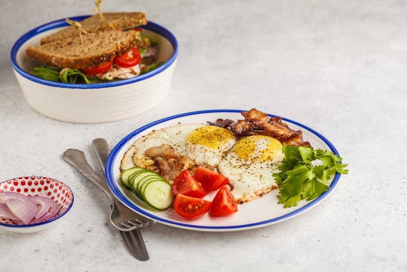 Smażący jajka z bekonem i kanapką z mięsem, serem i veget, obrazy royalty free