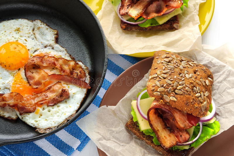 Smażący jajka z bekonem w obsadzie odprasowywają nieckę jak kanapki i fotografia stock