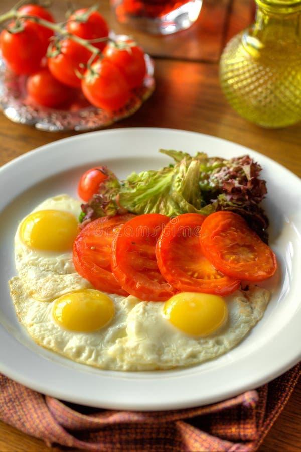 Smażący jajka z piec pomidorami obraz royalty free
