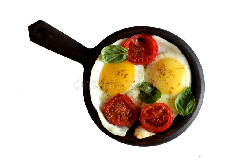 Smażący jajka z pomidorowymi plasterkami, korzennymi pikantność i basilem w niecce odizolowywającej na białym tle, obraz royalty free