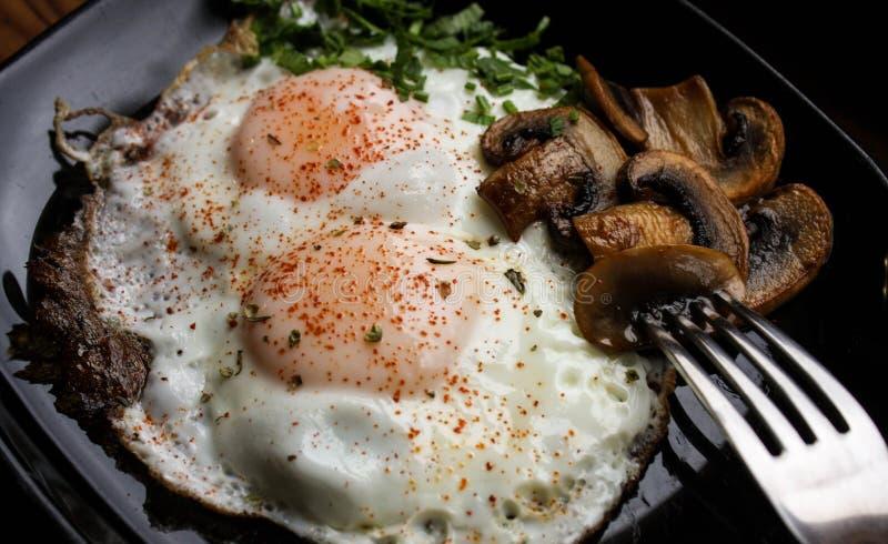Smażący jajka z ziele i pieczarkami najlepszy widok zdjęcia royalty free