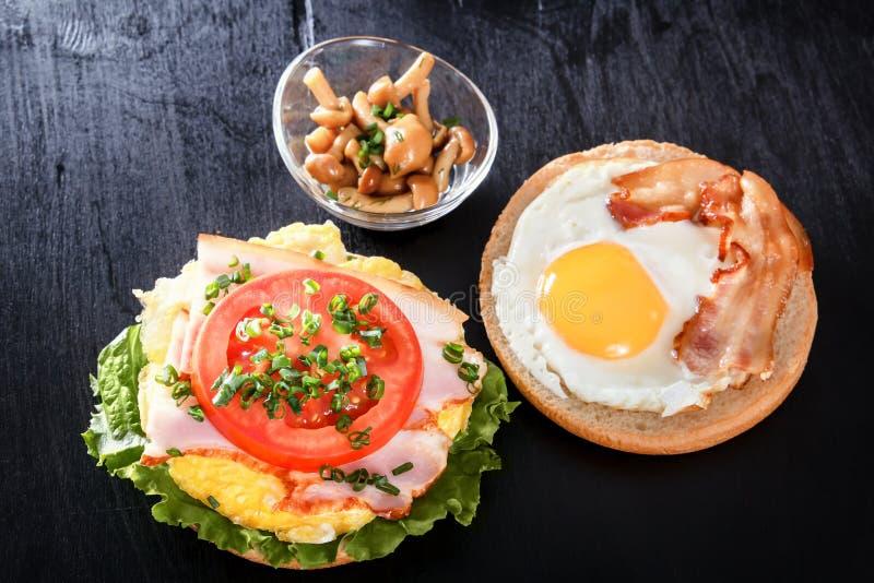 Smażący jajko na rolce Kanapka z bekonem, pomidorem i warzywami, Pieczarki śniadanie obrazy stock