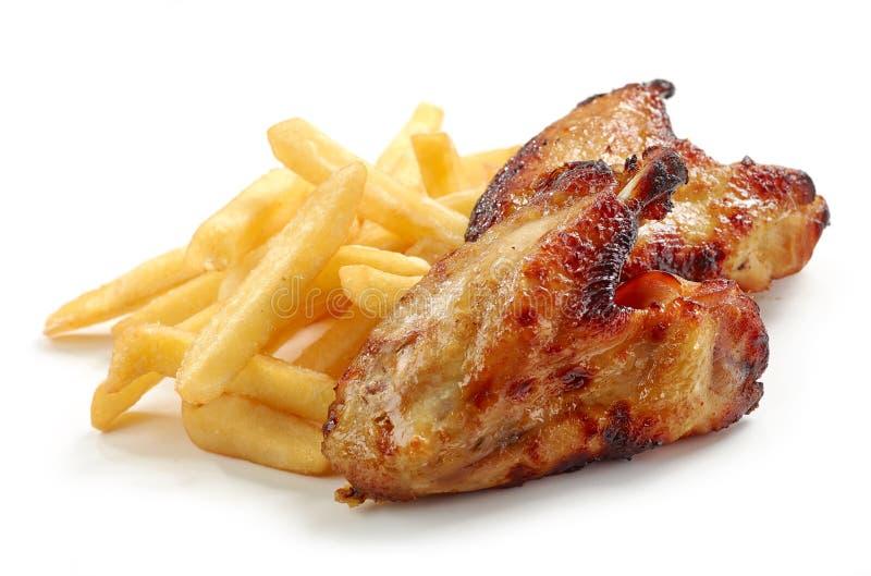 Smażący kurczaków skrzydła i grule fotografia royalty free