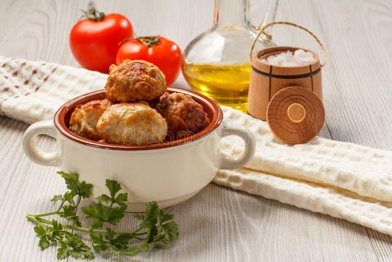 Smażący mięśni cutlets w ceramicznym zupnym pucharze, czerwoni pomidory, szklana larwa zdjęcia stock