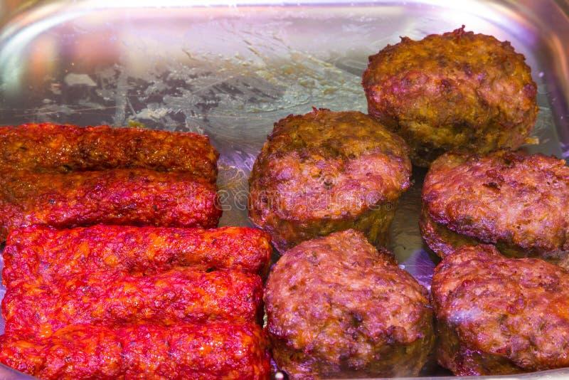 Smażący mięśni hamburgery i kiełbasy obraz stock