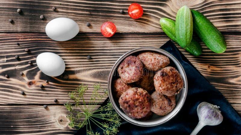 Smażący mięśni paszteciki w pucharze, dwa jajkach, czereśniowych pomidorach, czosnku i świeżych ogórkach, fotografia royalty free