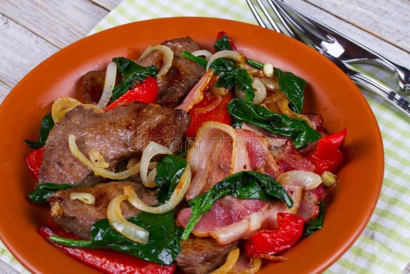 Smażący mięso, bekon, czerwony papryka pieprz i szpinaka talerz, obraz royalty free