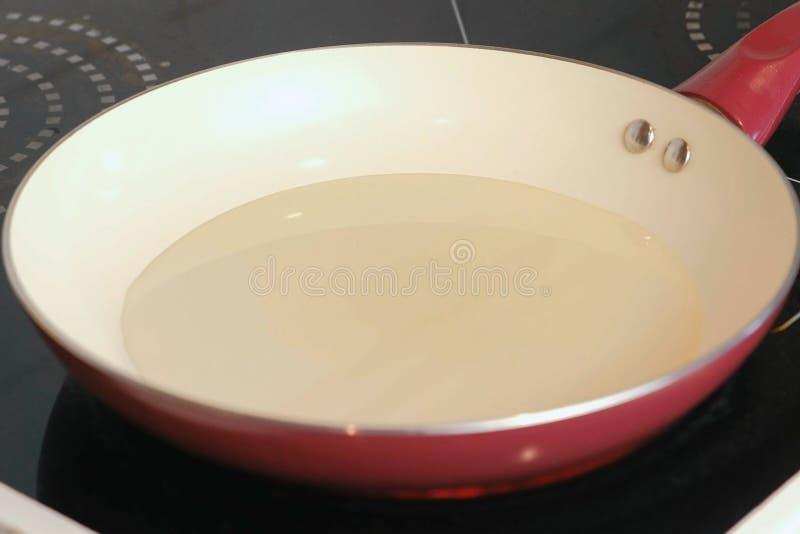 Smażący nieckę z słonecznikowym olejem ogrzewa na elektrycznej kuchence obraz stock