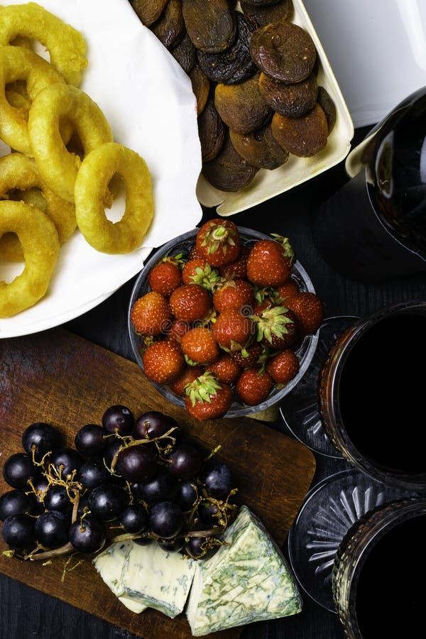 smażący ośmiornicy calamari z winogronem lub kałamarnicy, wysuszona morela, truskawka, butelka czerwone wino, dwa szkła zdjęcie stock