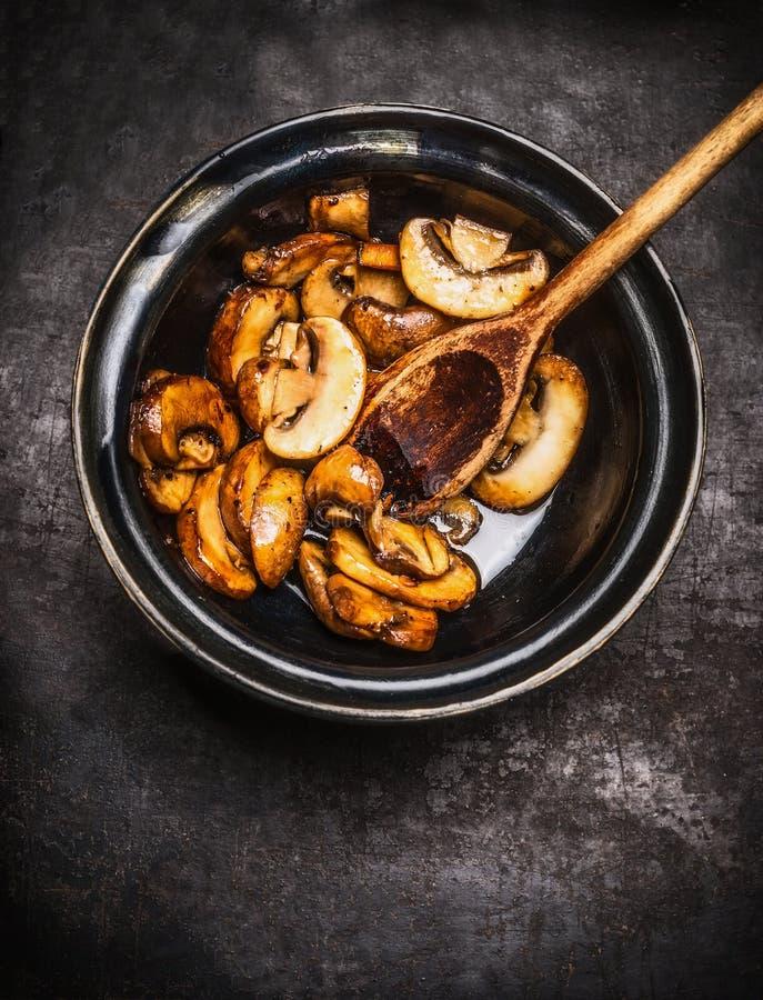Smażący szampiniony w pucharze z kulinarną łyżką na ciemnym nieociosanym tle zdjęcia royalty free