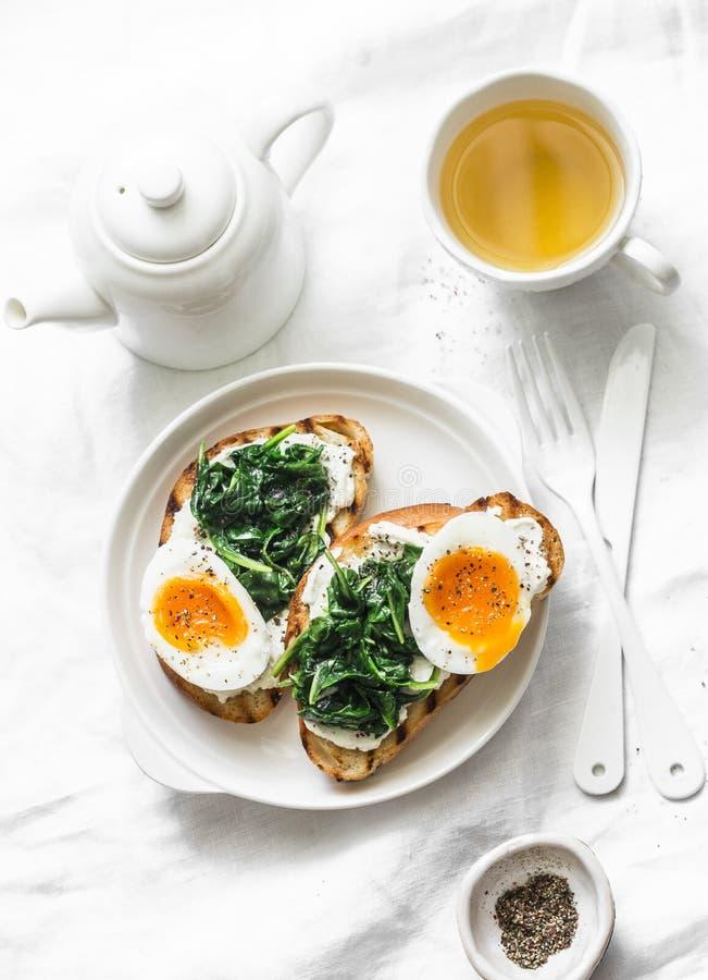 Smażący szpinaki, labne, gotowane jajko kanapki i zielona herbata, - wyśmienicie zdrowa przekąska na lekkim tle lub śniadanie fotografia stock