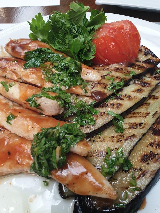 Smażący w nafcianym kurczaku, oberżynie i pomidorach na bielu talerzu, obraz stock
