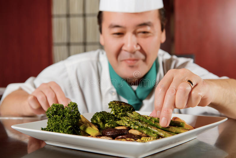 Smażący warzywa gotujący szefem kuchni obrazy stock