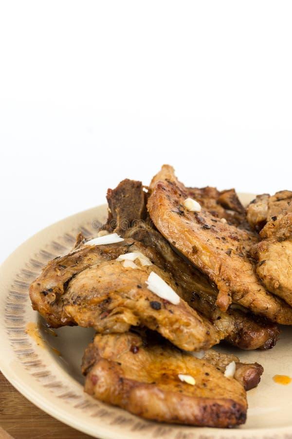 Smażący wieprzowina kotleciki słuzyć na talerzu odizolowywającym nad białym tłem obrazy stock