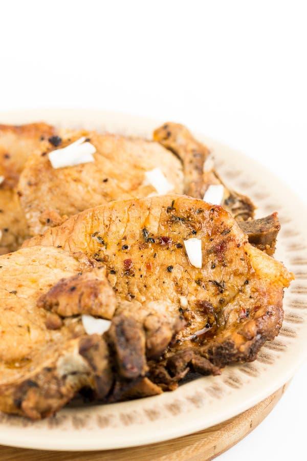 Smażący wieprzowina kotleciki słuzyć na talerzu odizolowywającym nad białym tłem zdjęcie stock