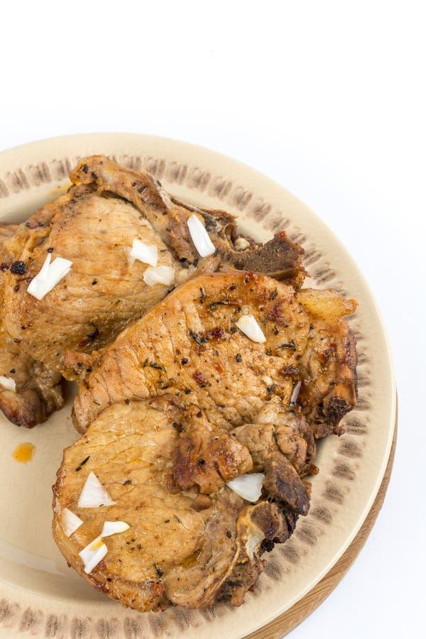 Smażący wieprzowina kotleciki słuzyć na talerzu odizolowywającym nad białym tłem obraz stock