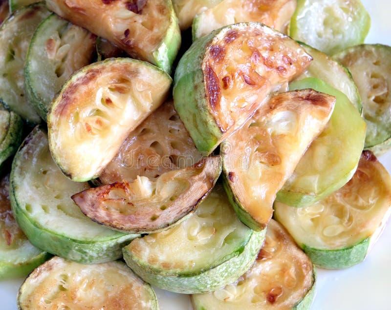 Smażący zucchini plasterki na bielu talerzu zdjęcie royalty free
