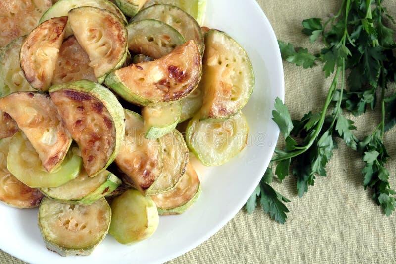 Smażący zucchini plasterki na bielu talerzu z zieleniami fotografia stock