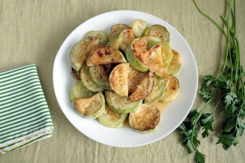 Smażący zucchini plasterki na bielu talerzu z zieleniami fotografia royalty free